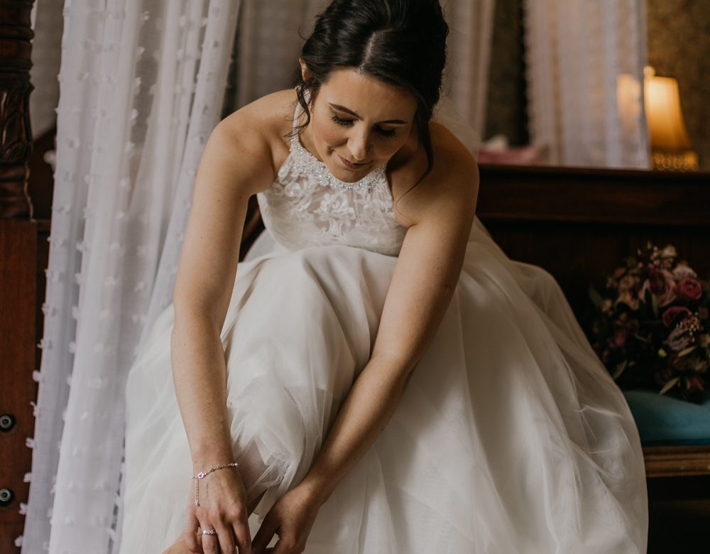 bride getting ready the morning of of her wedding timing her shoes